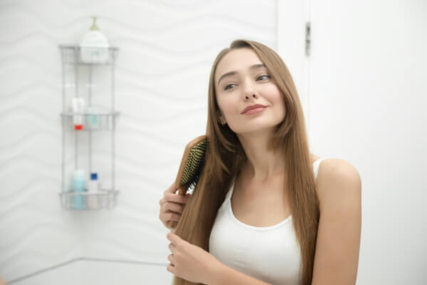 Woman brushing long, straight hair.
